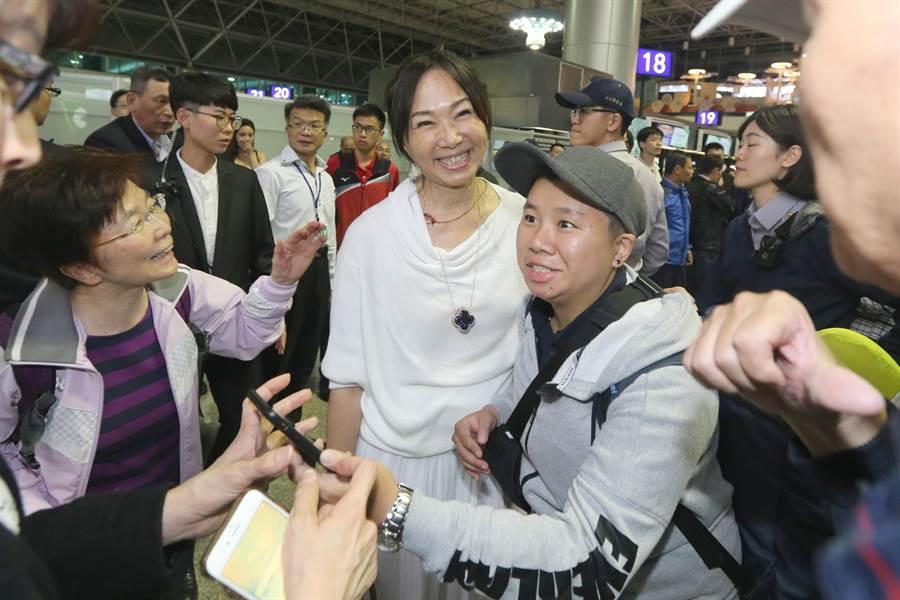 韓國瑜在接受媒體訪問時,在一旁的李佳芬也受到旅客的包圍要求合影,她也親切回應。(陳麒全攝)