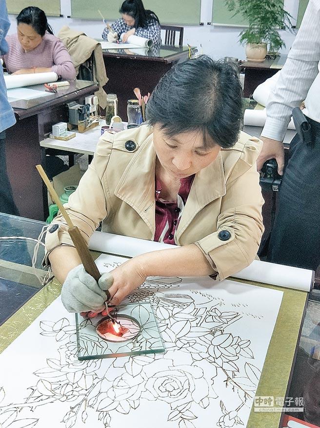 大陸河南南陽的烙畫師,正用數百度高溫的鐵筆烙燙做畫。(記者陳君碩攝)