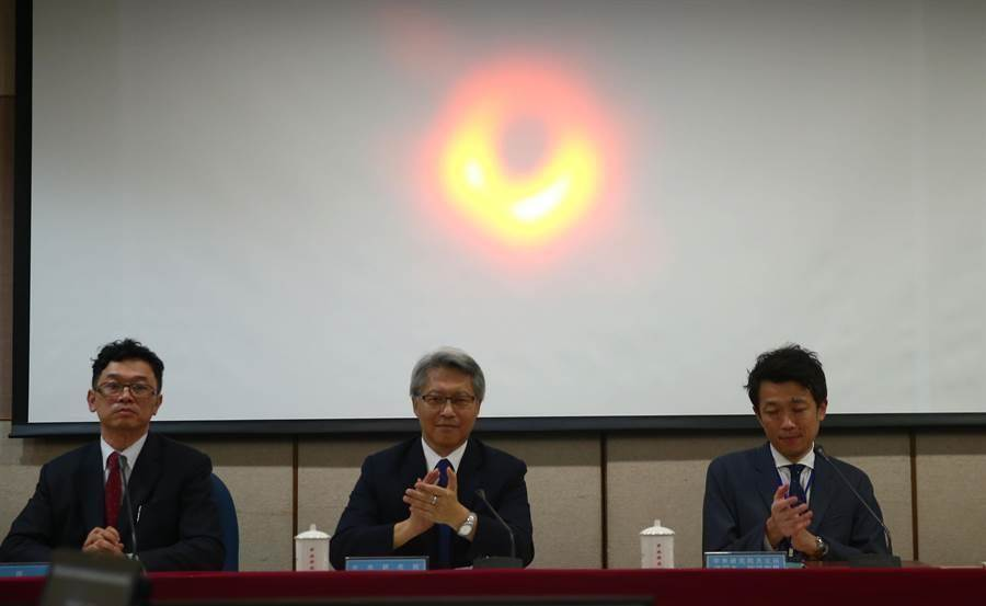 事件視界望遠鏡(EHT)計畫與中央研究院、科技部共同舉辦全球同步記者會,發表全球首張黑洞照片。包括台北在內共6座國際城市(比利時布魯塞爾、智利聖地牙哥、中國上海、台灣台北、日本東京和美國華府)同步直播發布。中研院院長廖俊智(中)主持台北現場記者會,螢幕上則為首度拍到的黑洞畫面。(陳信翰攝)