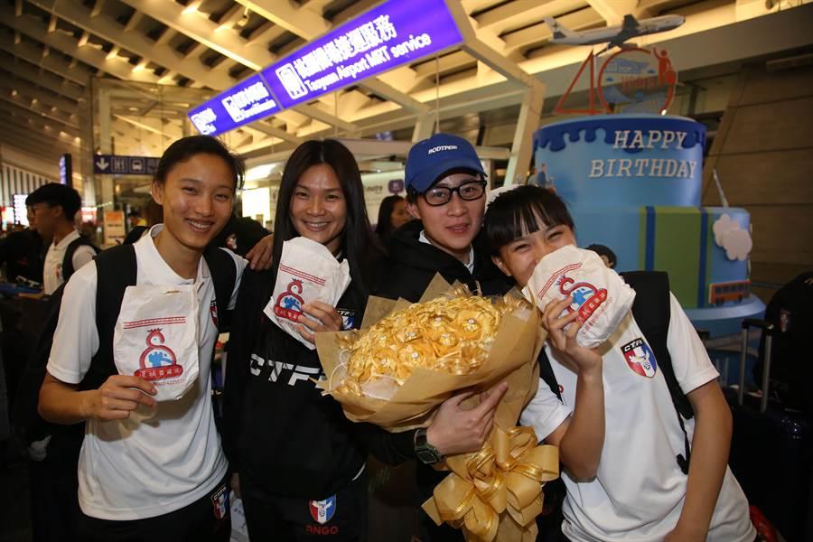 中華女足包欣玄(左起)、王湘惠、陳燕萍回到台灣立刻在機場大啖雞排。(李弘斌攝)