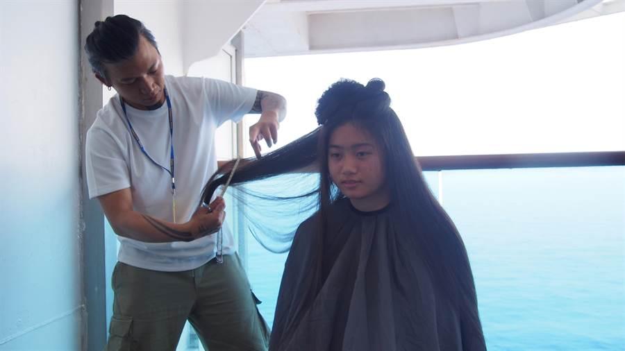 寓WEST SALON & BAR髮型設計師SAM讓學童在郵輪上體驗剪髮。(李侑珊攝)