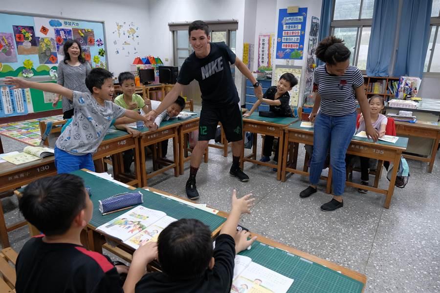 來自巴西的交換學生張冠杰,被小朋友拉說「老師教我們打藍球!」(羅浚濱攝)