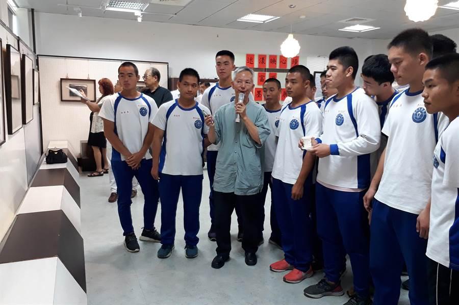 林富源(持麥克風者)在水里商工展出25件精品水墨,並向學子解說導覽。(沈揮勝攝)