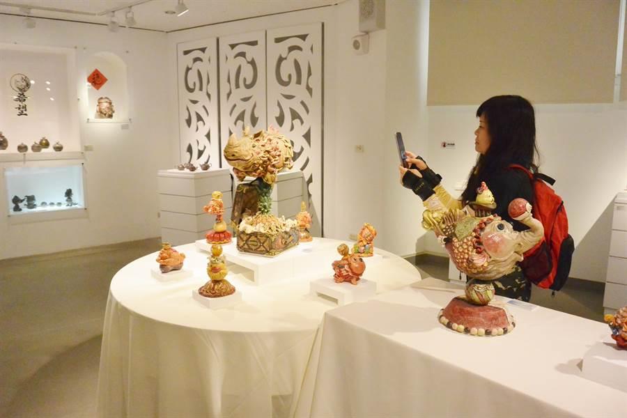 參觀展覽的民眾欣賞陳宣亦創作的「犀旺綻放希望」,並拍照留念。(巫靜婷攝)