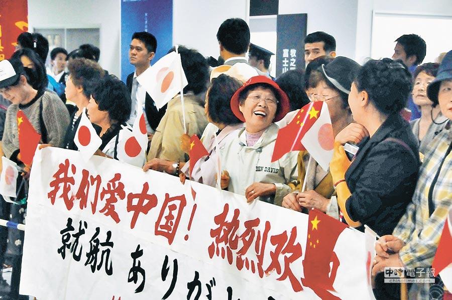 日本民眾在靜岡機場手舉橫幅與中日兩國國旗熱情歡迎陸客。(新華社資料照片)