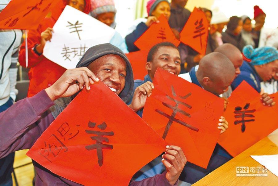 南京農業大學的非洲留學生用毛筆寫「羊」,迎接羊年。(中新社資料照片)