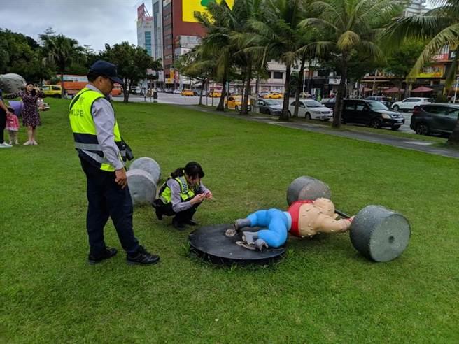 花蓮站前廣場「大師兄」舉重公仔不知原因倒下,警方到場調查是否遭人為破壞。(許家寧攝)