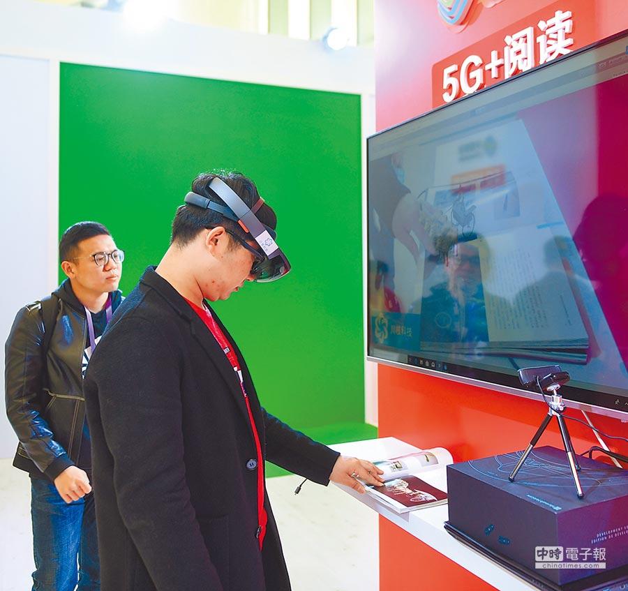 第5屆中國數位閱讀大會12日在杭州舉行,觀眾在數位閱讀發展與技術博覽會上體驗5G+閱讀。(新華社)