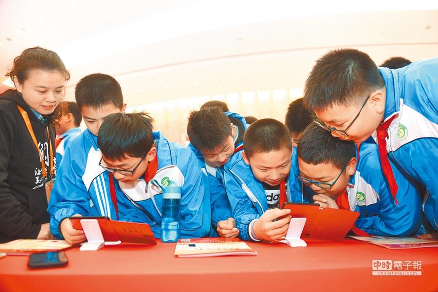 一群小學生使用3C產品閱讀電子書。(新華社)