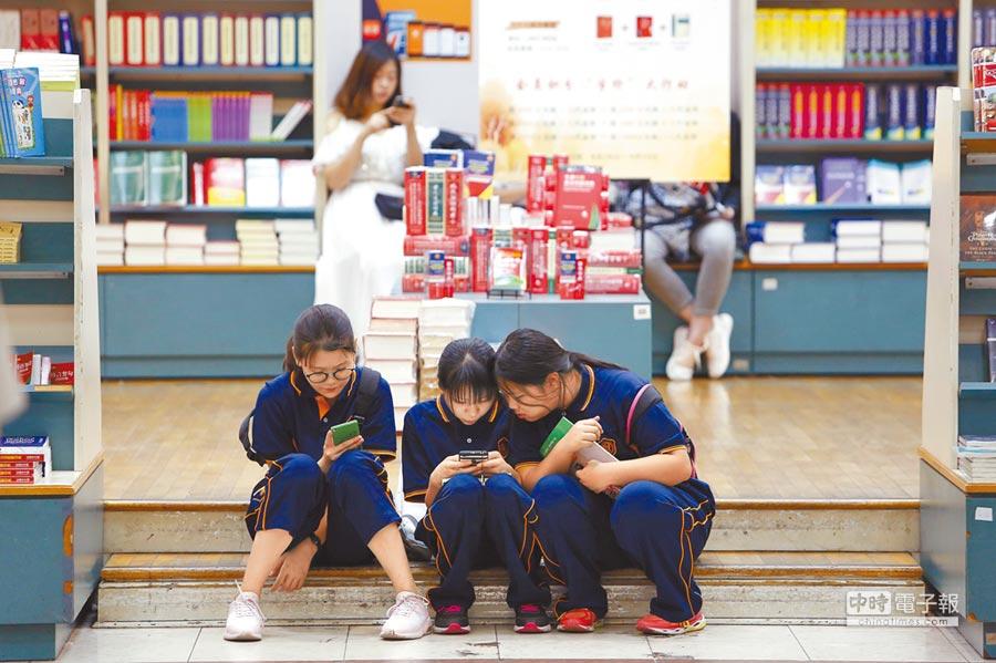 上海一家書店內,幾名女孩在查閱手機的相關信息。(中新社)