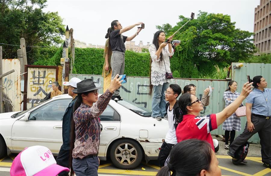 大甲媽祖回鑾,15日進入台中市經過烏日、大肚、龍井,有民眾為拍下媽祖鑾轎,連路邊老舊汽車都爬了上去了。(黃國峰攝)