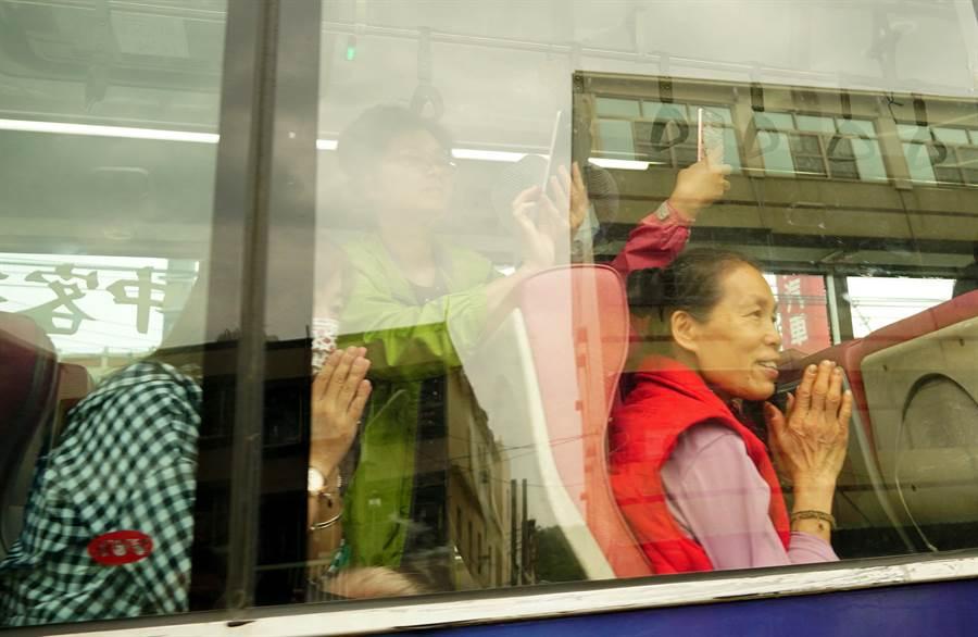 媽祖遶境台中15日很熱鬧,大甲媽和白沙屯媽,15日上午相繼進入台中市,一輛公車經過媽祖鑾轎,乘客紛紛雙手合十祭禱。(黃國峰攝)