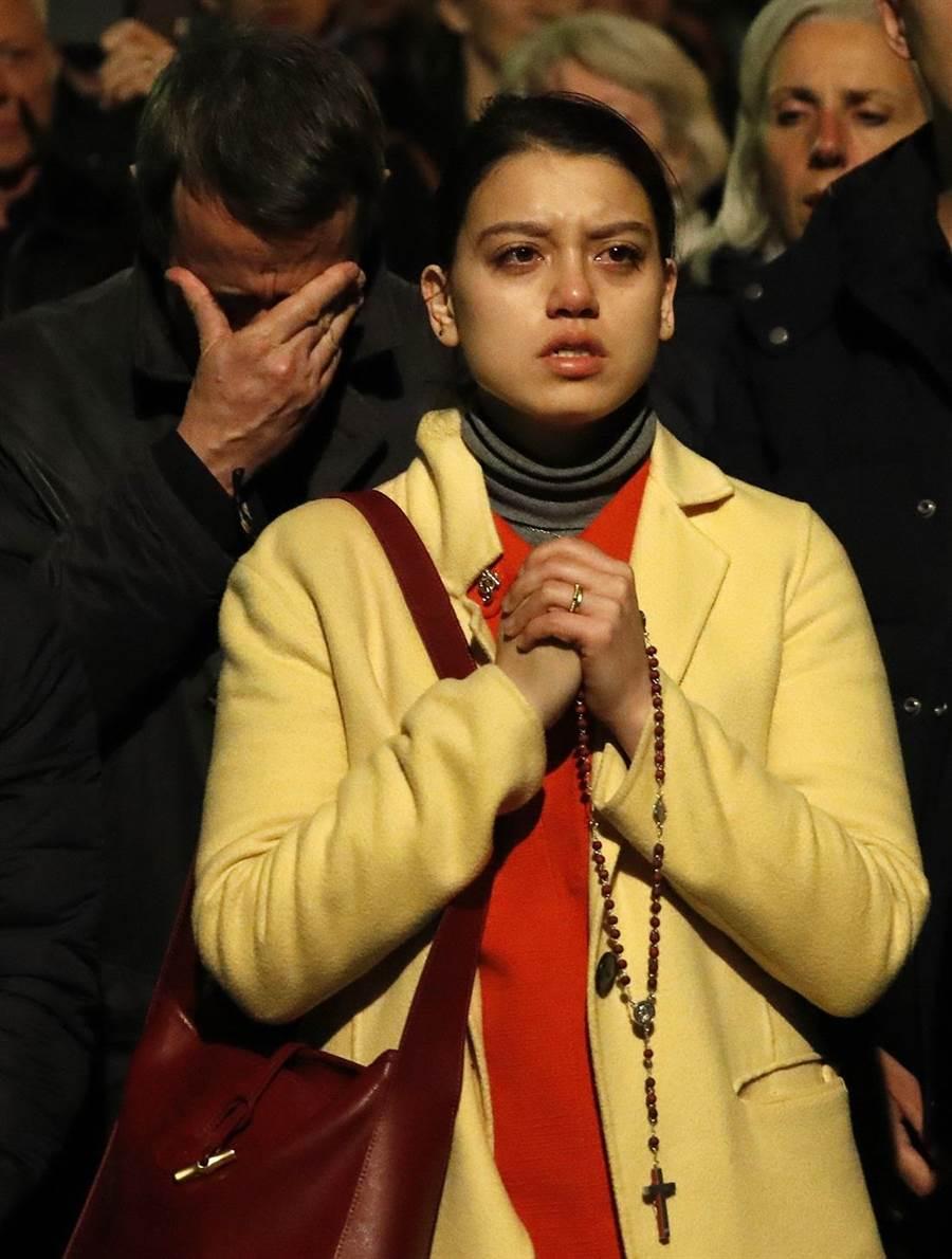 巴黎聖母院是法國人精神象徵,意義超越宗教,發生大火讓法國人心碎了,當地居民守在現場默默垂淚、禱告。(圖/美聯社)