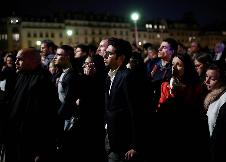 巴黎聖母院是法國人精神象徵,意義超越宗教,發生大火讓法國人心碎了,當地居民守在現場默默垂淚、禱告。(圖/路透社)