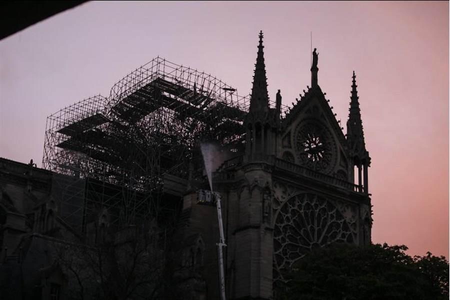 圖為巴黎消防隊員在日出時看到發生災難性大火的巴黎聖母院。(美聯社)