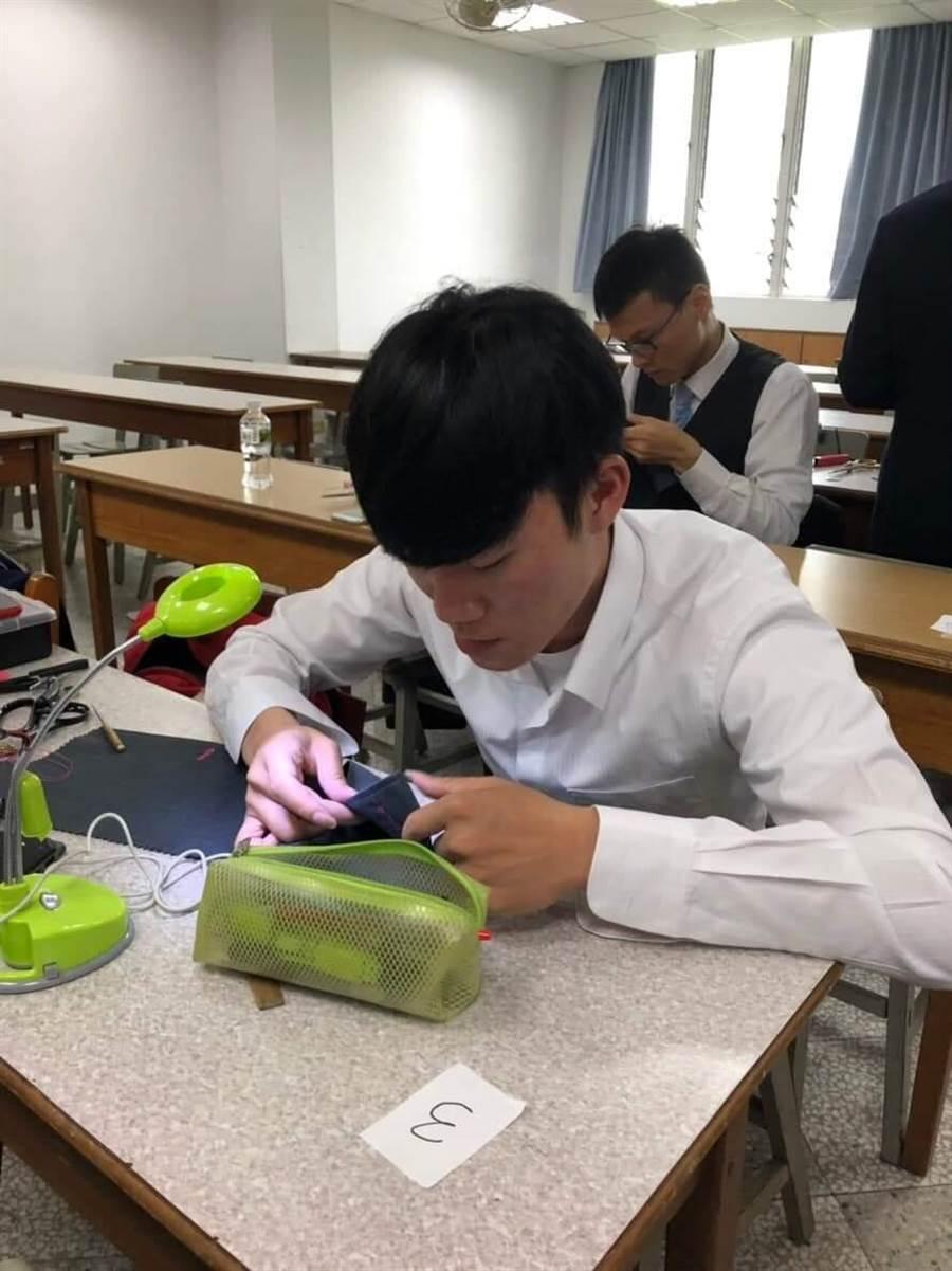 亞洲大學時尚系學生陳泓誠參加「洋服縫製公開賽」時專注的製作衣服。(林欣儀翻攝)