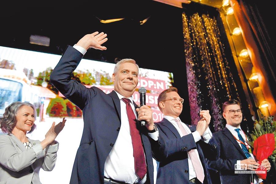 芬蘭社會民主黨黨魁林奈(中揮手者)14日偕同妻子(左)與社民黨秘書長(右二)共同慶祝勝選。(法新社)