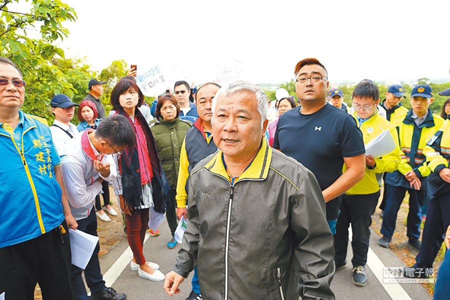 竹北市長何淦銘15日與多名市代赴第六公墓拓寬工程現勘,遇到自救會舉牌陳抗。(徐養齡攝)