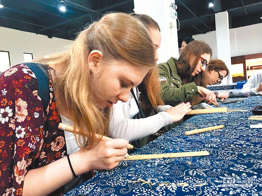 2017年5月16日,來自帶路沿線國家留學生在安徽黃山市體驗徽州竹雕。(新華社)