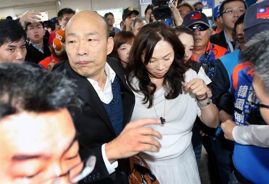 高雄市長韓國瑜(左)18日返抵國門,由於接機民眾過於熱情,場面一度混亂失控,在警方開道護送下,韓國瑜緊摟著妻子李佳芬(右)快步離開機場。(范揚光攝)