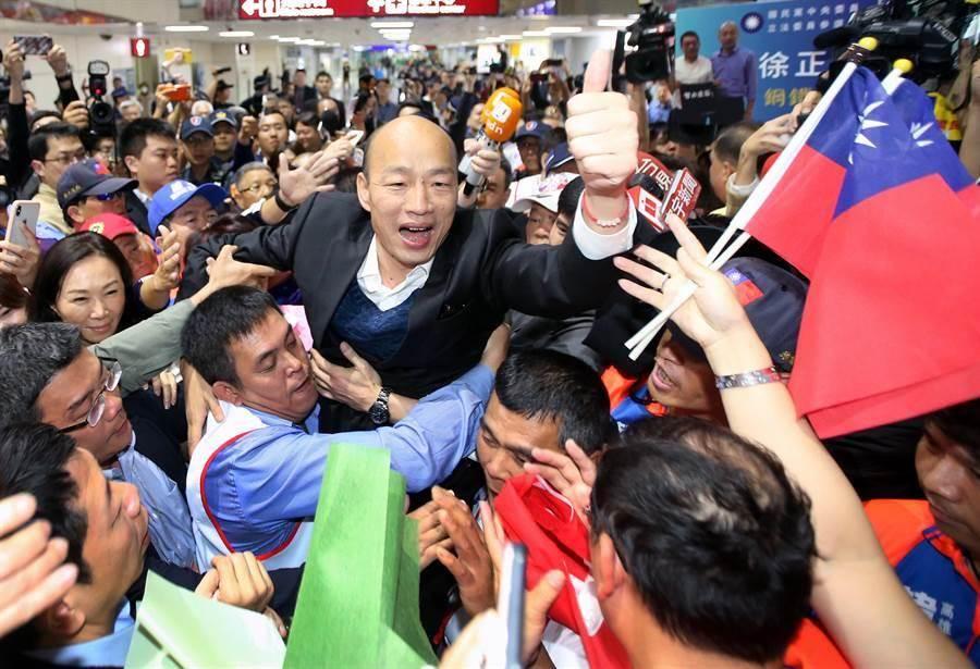 高雄市長韓國瑜(中)18日返抵國門,大批熱情民眾前往機場接機,熱情支持者將韓國瑜高高抬起,接受群眾歡呼。(范揚光攝)