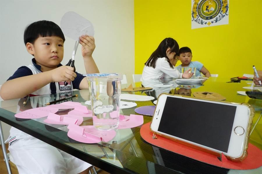 7歲王首承(左)創作「多功能可折疊杯墊」長達2個月,期間失敗多次,還因紙張較厚,不小心剪到手。(王文吉攝)