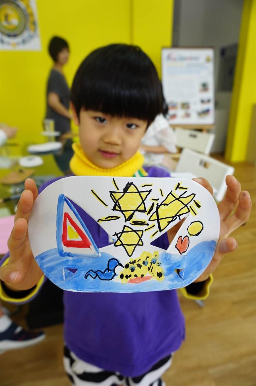 5歲羅儒悌展示自己創作發明的「多功能可折疊杯墊」,作品還有可愛手繪圖案。(王文吉攝)
