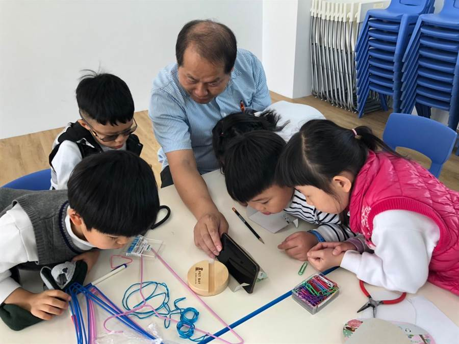 聯合大學工業設計系副教授徐義權,指導6位學童創作「多功能可折疊杯墊」。(王文吉攝)