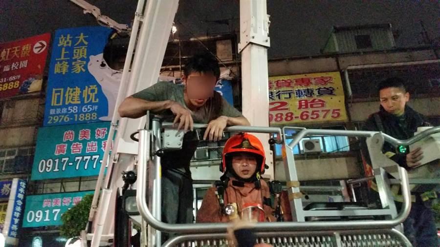 三重公寓火警,5樓頂民眾獲救由雲梯車接下。(吳家詮翻攝)