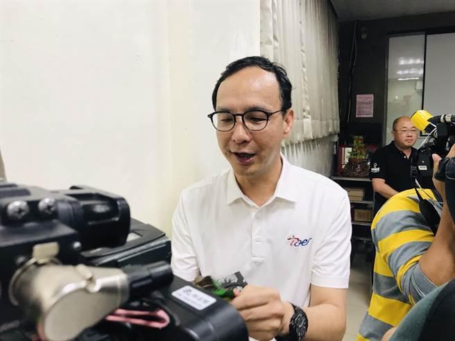 前新北市長朱立倫19日參訪新北市瑞芳區的食品工廠,將豆類食品遞給記者,請記者吃。(張穎齊攝)