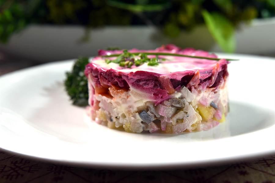 用鯡魚肉、紅蘿蔔、馬鈴薯與洋蔥層層堆疊的〈甜菜根鯡魚沙拉〉,形色味皆很誘人,又稱「空著皮草的鯡魚」。(圖/姚舜)
