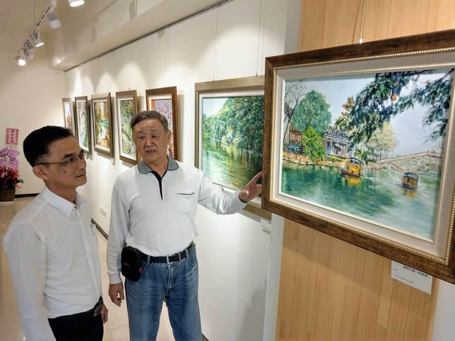 70歲許俊傑(右)個展,向永豐銀行經理謝璨隆(左)說明作品意涵。(范振和攝)