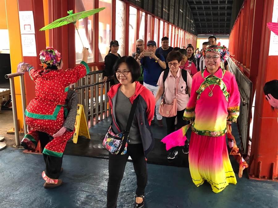 縣府今天特別安排民俗陣頭「公背婆」在碼頭迎接,讓初體驗的港客好開心。(李金生攝)