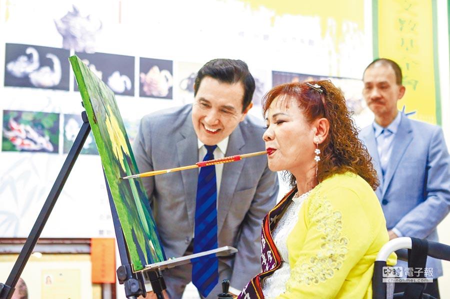 前總統馬英九(後左)18日出席周大觀文教基金會2019年熱愛生命獎章得主記者會,仔細端詳口足畫家高淑專(前)畫畫過程。(鄧博仁攝)