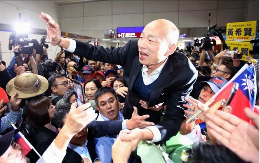 高雄市長韓國瑜(中)18日訪美回國,大批熱情民眾前往機場接機,熱情支持者將他高高抬起,韓國瑜也向大家揮手致意。(資料照片,范揚光攝)