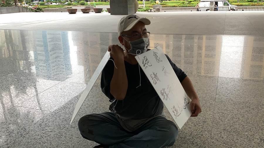 有一男子戴著口罩與帽子,在高雄市政府靜坐,身上的牌子寫著「國民黨黑箱作業卡死韓市長」、「絕食請求韓市長選總統」。(柯宗緯攝)