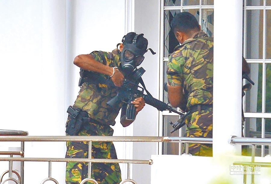並展開緝捕可能涉案凶嫌,圖為該國特種部隊士兵正準備搜索一間可疑的民宅。(法新社)