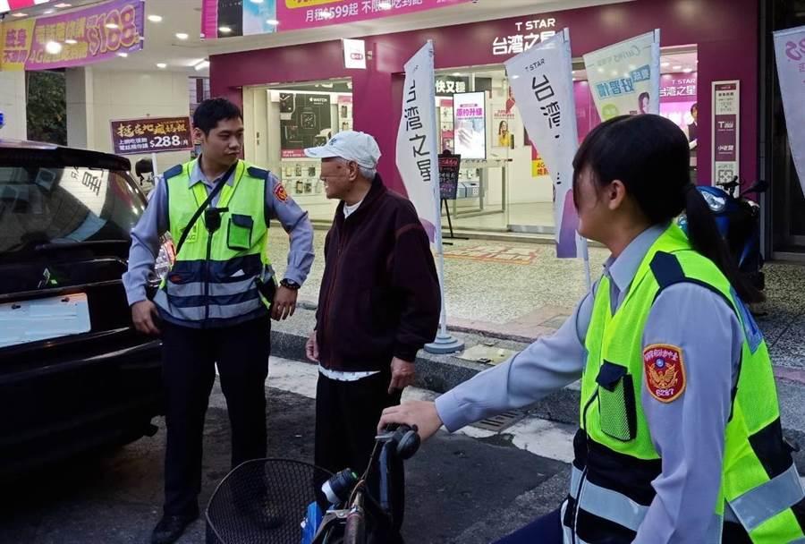台中市警察局第六分局何安派出所員警,與迷途老翁比手畫腳,通知家人帶老翁順利返家。(盧金足翻攝)