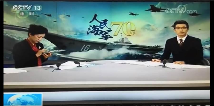 大陸央視在直播青島中共海軍檢閱儀式時,低頭滑手機的畫面不慎播了出去。(圖/網路視頻截圖)