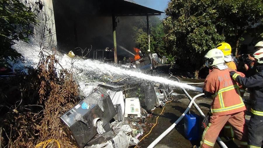 鐵皮倉庫堆置大量回收的廢棄排油煙機,火勢驚人,消防人員布水線灌救近一個小時才撲滅火勢。(謝瓊雲攝)