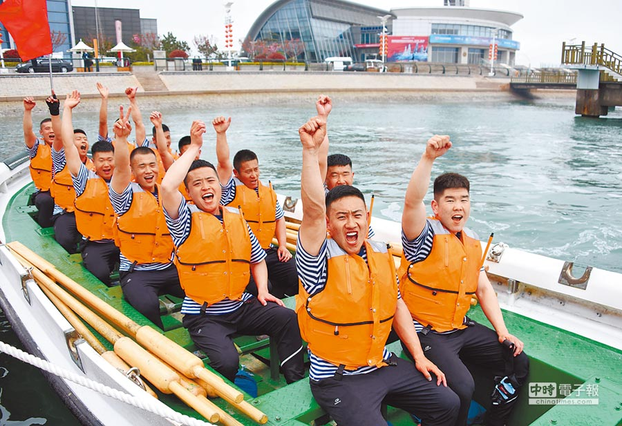 解放軍海軍成立70周年多國海軍活動舢舨比賽24日在青島奧林匹克帆船中心舉行,解放軍海軍代表隊在獲勝後慶祝。(新華社)