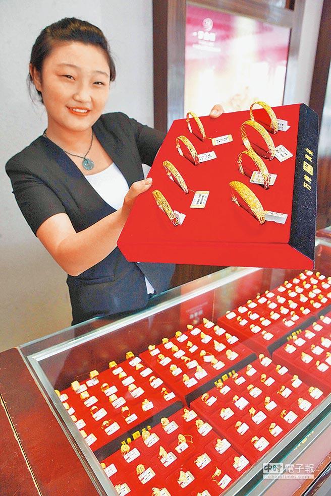 江蘇省贛榆縣一家金店營業員展示黃金飾品。(新華社資料照片)