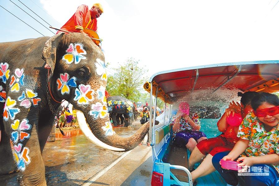 4月11日,泰國舉行活動迎接潑水節,大象向車上的遊客噴水。(新華社)