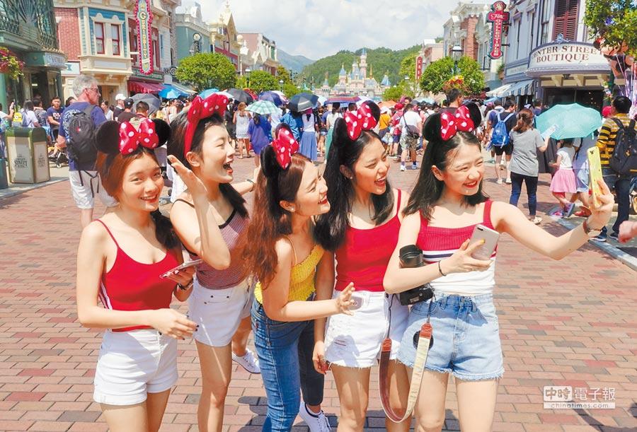 一群遊客在香港迪士尼樂園自拍賣萌。(中新社資料照片)