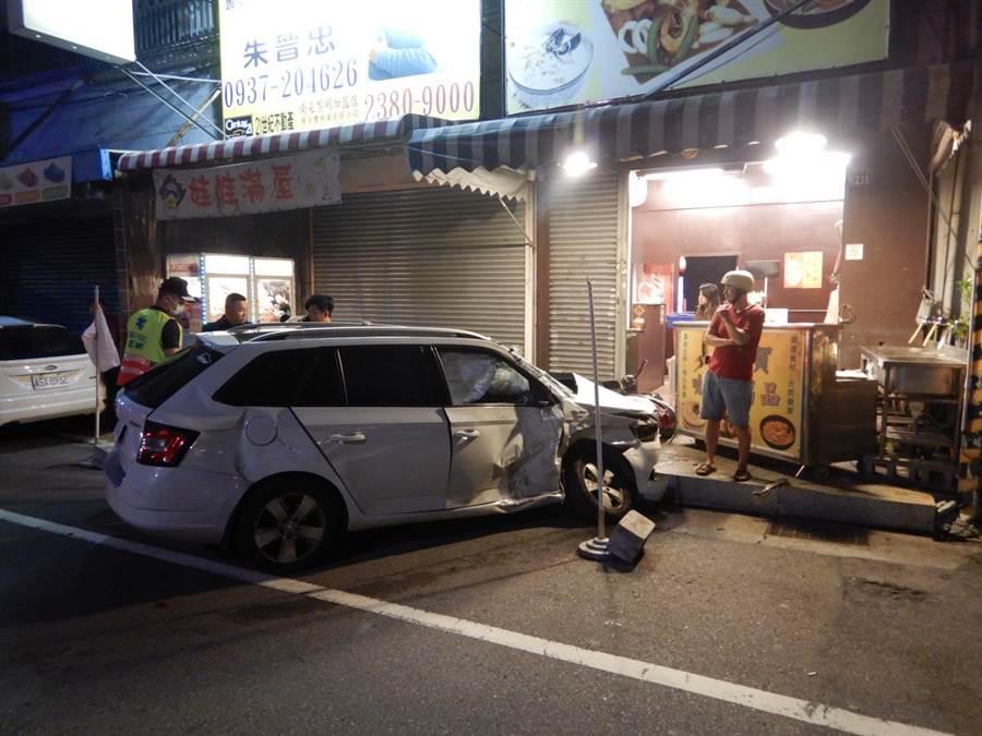 白色轎車與救護車相撞後,又衝路路旁店家,導致店家擺放在門口的攤子都被撞受損。(林欣儀翻攝)