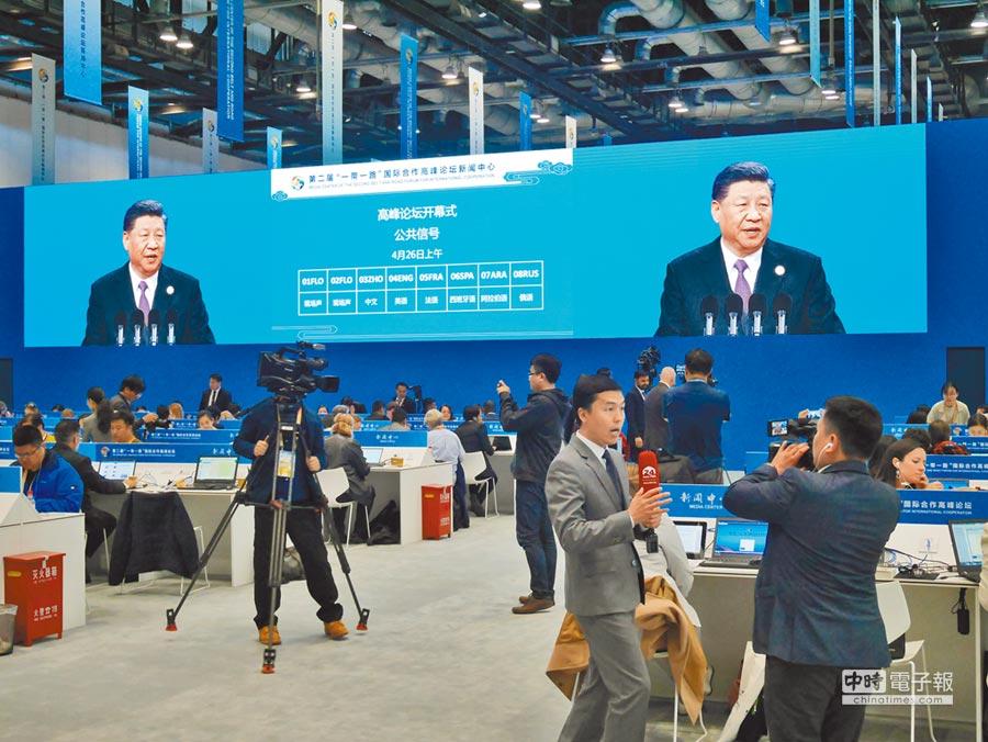 大陸國家主席習近平26日在一帶一路高峰論壇開幕式上演講,新聞中心觀看直播的記者即時做報導。(記者陳君碩攝)