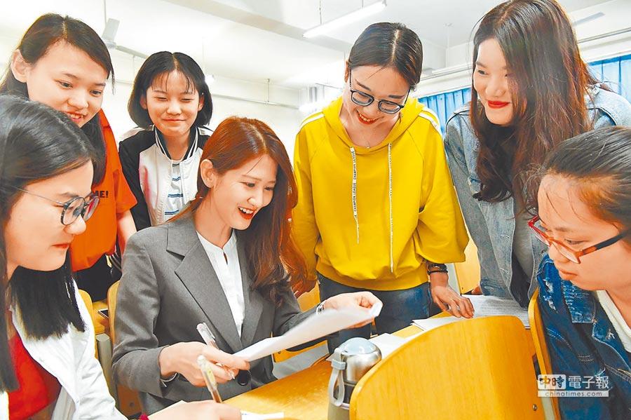 台灣女孩翁如辰(中坐者)嫁到河北後,在河北師大商學院任教,圖為翁如辰與學生討論功課。(中新社資料照片)