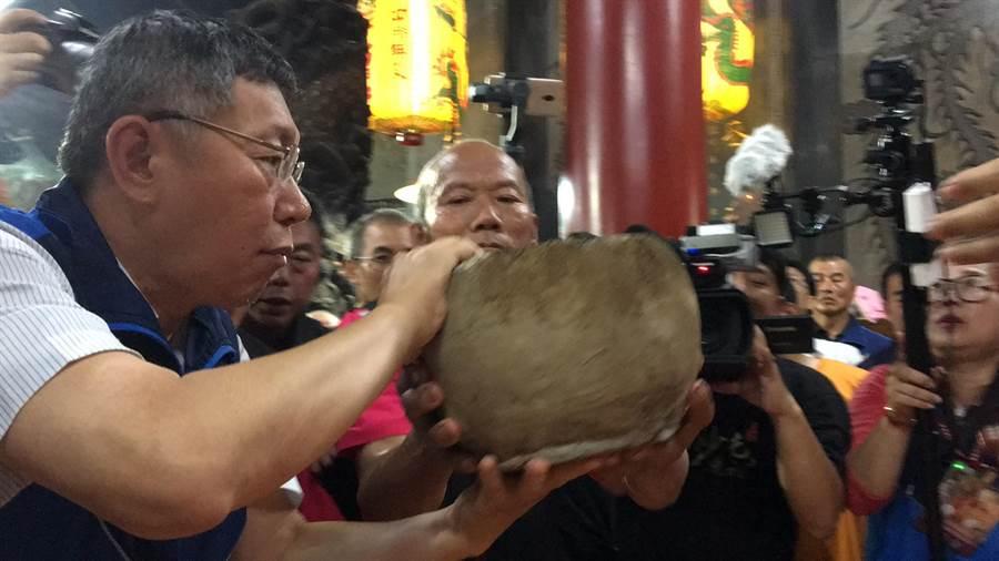 台北市長柯文哲從拱天宮主委洪文華手中接過火缸,準備交由值年爐主進行合爐儀式。(白沙屯拱天宮提供)