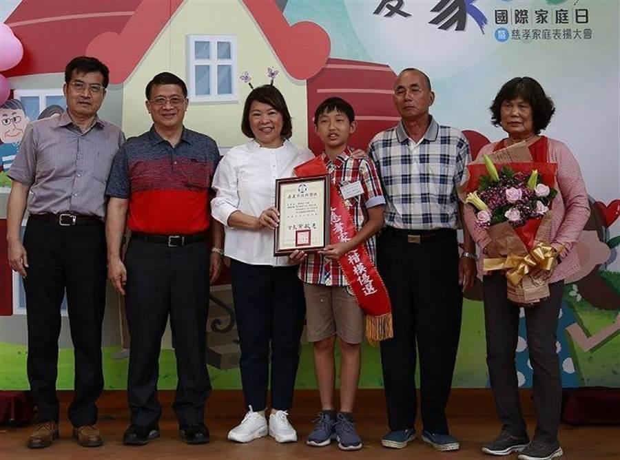嘉義市長黃敏惠(左三)表揚僑平國小學童賴宥礽與阿公阿嬤為慈孝家庭楷模。(廖素慧攝)