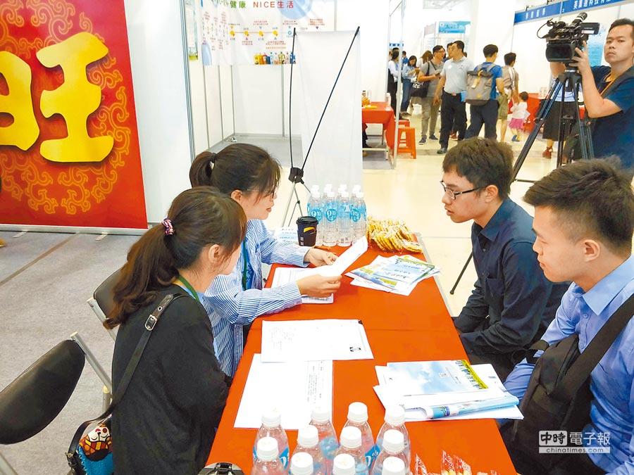 上海市台灣同胞投資企業協會第三屆徵才博覽會,昨首次移師高雄舉行。圖為旺旺集團工作人員與應聘者面談。(中新社)